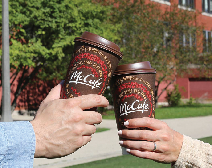 two people clinking McDonald's coffee cups