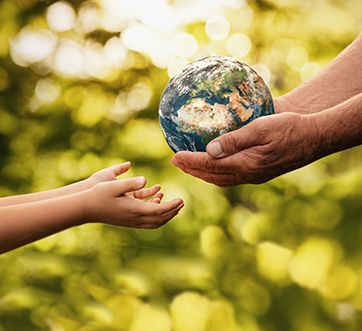 adult hands handing globe to child's hands