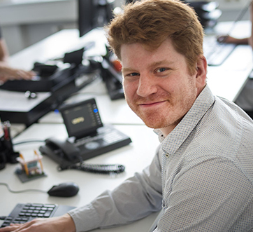 young redheaded man at his desk, smiling