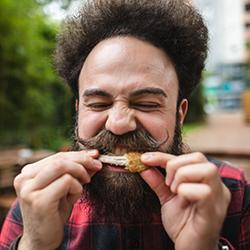 Hipster w handlebar mustache eating chicken