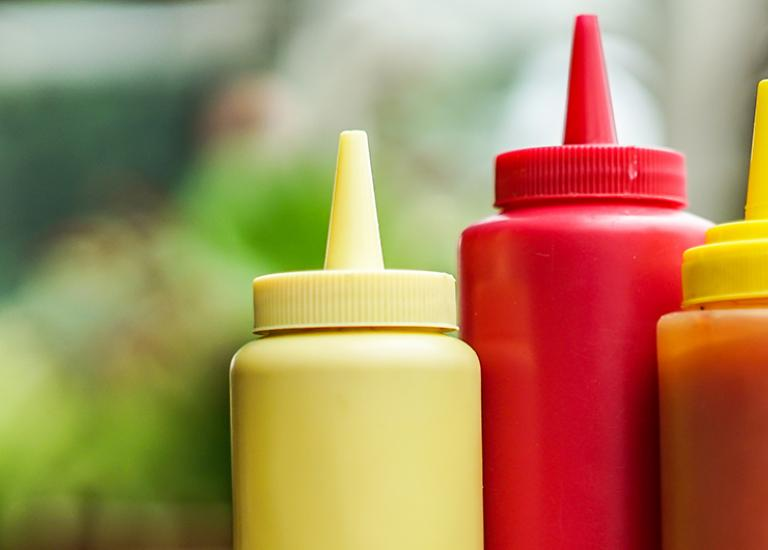 close-up of ketchup, mustard and hot sauce squeeze bottles