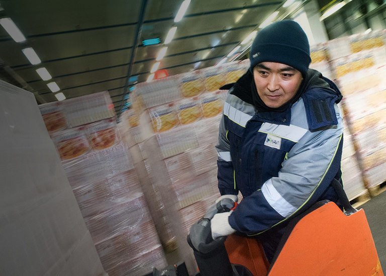 Distribution roles - Asian DC worker driving pallet into place