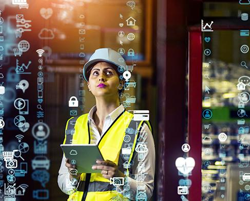woman in hardhat and safety vest looking at 3D interface floating before her
